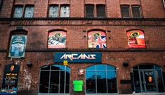 The outside of ArCains with their logo on a brick wall.