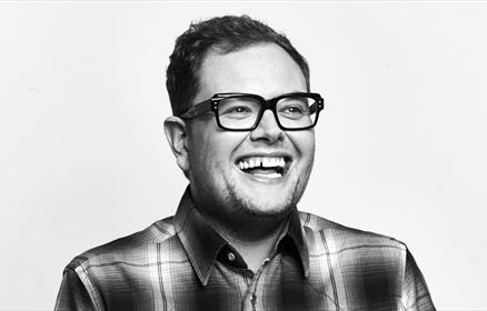 A black and white photo of Alan Carr.