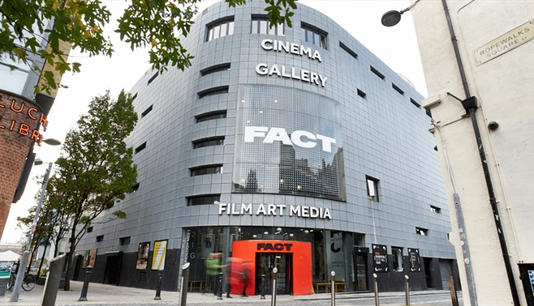 Front entrance to FACT with an orange door, grey brickwork and a large LED screen on the front of the building.