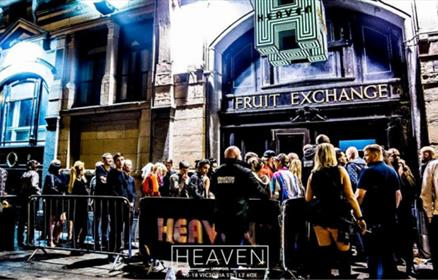 A large crowd queue up outside of a nightclub. A giant H light lights up the street