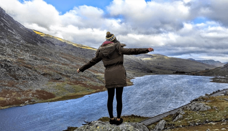 A lady stood on a rock looking out over a lake in the mountains.