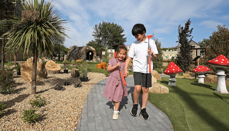 Two children on a miniature golf course.