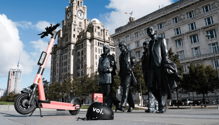 Voi scooter with a voi branded helmet in front of The Beatles statue on Liverpool's Pier Head.