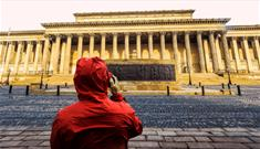 Person in a red coat taking a photo of St George's Hall.