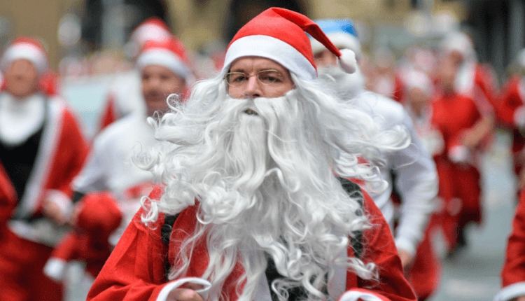 Man dressed up in a red santa costume with a long white beard running.