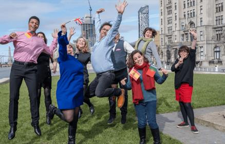 A group of people on a tour in front of the Royal Liver Building
