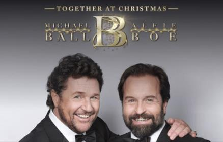 Michael Ball and Alfie Bow wearing suits against a grey background.