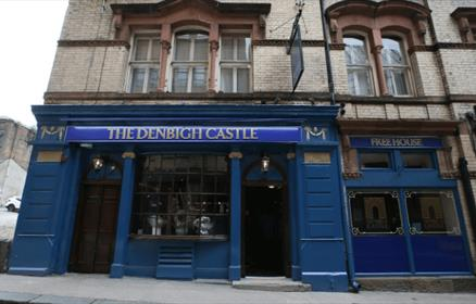 The exterior of the pub is a traditional, victorian facade painted blue with gold detail.