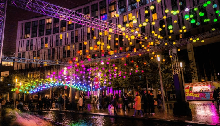 Multicoloured lights in spheres are suspended over the water in the shape of a wave