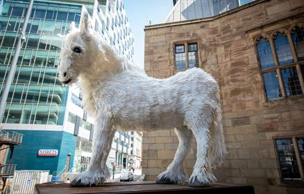 A large white horse sculpture, made from milk containers.
