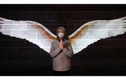 A projection of wings on a dark wall with a lady wearing a face covering. She is standing with her hands in prayer and the wings create the illusion o