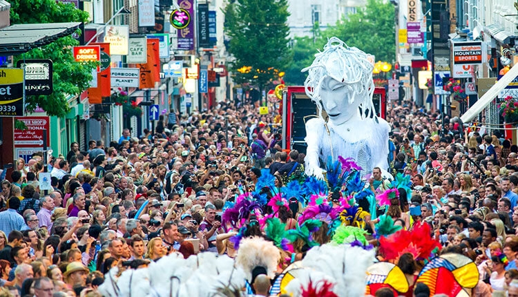 Crowds gather for a parade on Liverpool's Bold Street. A giant white puppet is led by dancers with colourful headdresses.