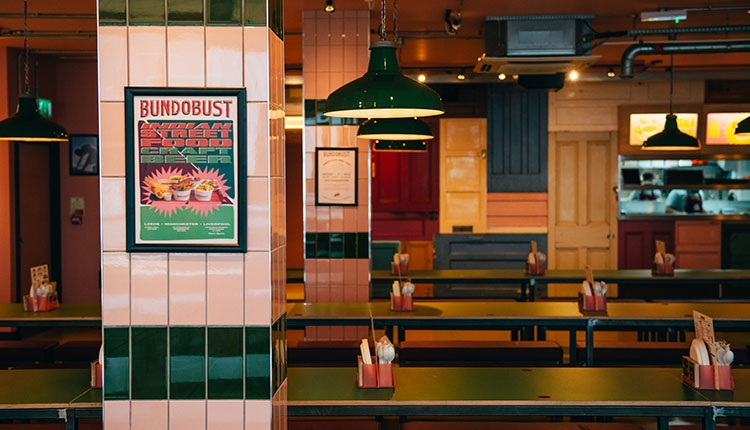 Inside of Bundobust with a poster on a wall and empty tables.