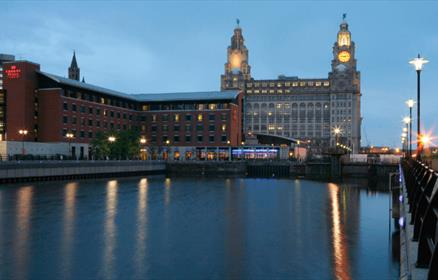 Exterior shot of the crown plaza with a large expanse of water in the foreground and the Royal Liver Building in the background.