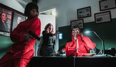 Two people are in red boiler suits inside a dark escape room. One woman in office wear points a gun at a masked person in a red boiler suit.