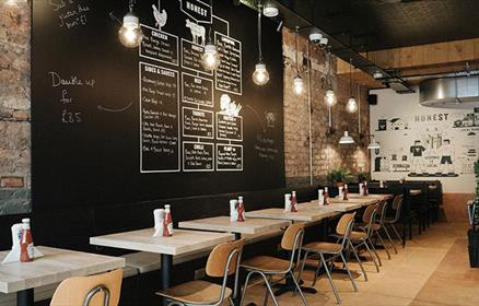 Inside of Honest Burger with empty row of tables and a chalk board wall.