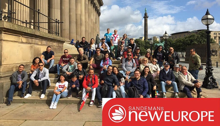 A group of tourists sit on the steps of St Georges Hall