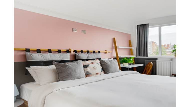 Selina bedroom with large double bed, pink walls and grey pillows.