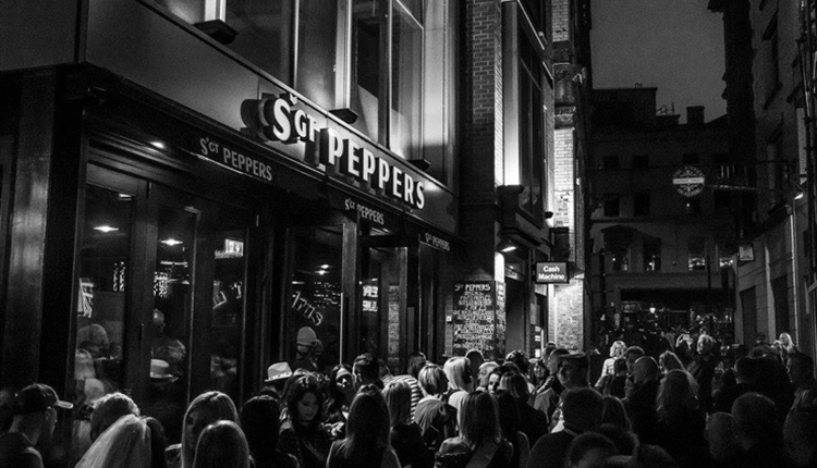 Sgt Peppers on Mathew Street - a black and white shot of the modern venue with crowds waiting to go in.