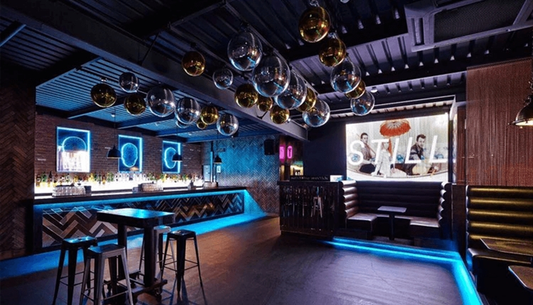 Soho Liverpool - an open space with blue neon floor lighting. Silver balls hang from the ceiling. Modern booth seating.