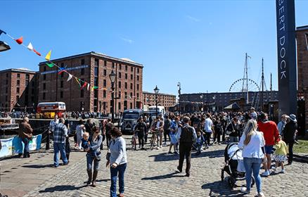 Families enjoy walking on the cobbles around the Royal Albert Dock in the sunshine. There's coloured bunting, a red double decker bus can be seen in t