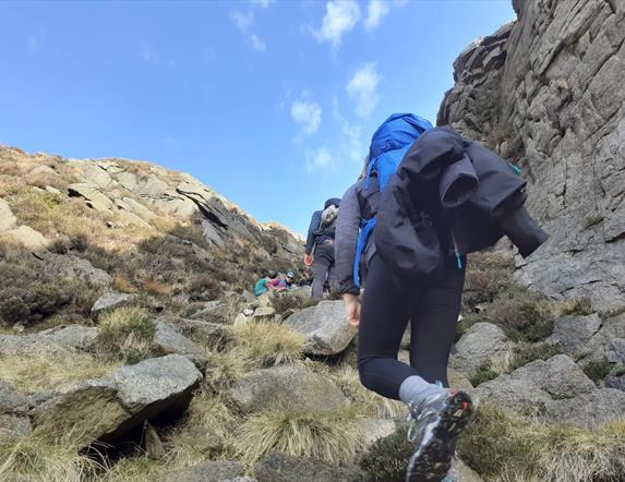 Image of people walking up a mountain.