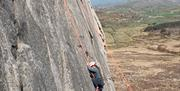 Image of a person scaling a mountain.