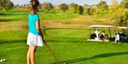 A young girl playing golf on a golf course.