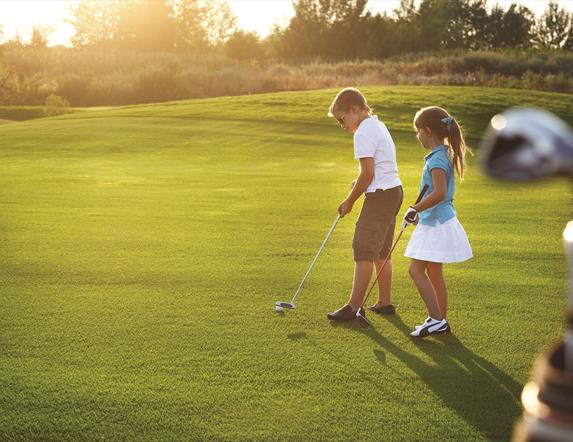 A young boy and girl playing golf on a golf course.