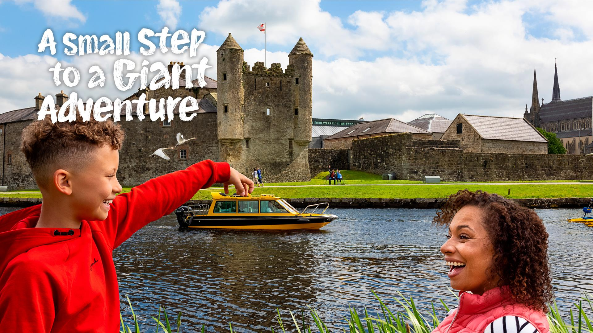 Image shows a boat in front of Enniskillen Castle with a boy and lady in the foreground looking like they're touching the boat