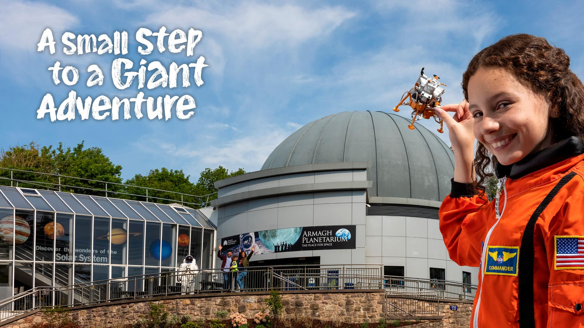 Image shows a girl in a spacesuit pretending to hold a spaceship on top of Armagh Observatory and Planetarium