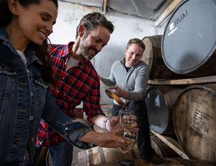 Couple enjoying a tour at Killowen Distillery whilst the guide pours liquid into a glass for sampling