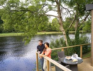 Couple relaxing and looking over their balcony onto the shores of scenic Lough Erne at Killyhevlin Lakeside Lodges, enjoying lunch.