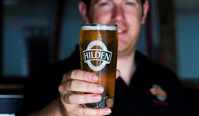 Image shows a smiling bartender holding a pint of Hilden beer