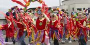 Image shows a parade of brightly dressed children