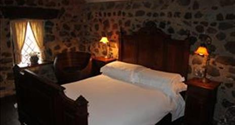 Image shows double bedroom with side tables and lamps