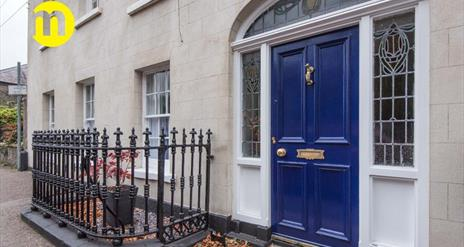 Image shows royal blue front door with iron railing to the left of the door Door leads out onto footpath on street