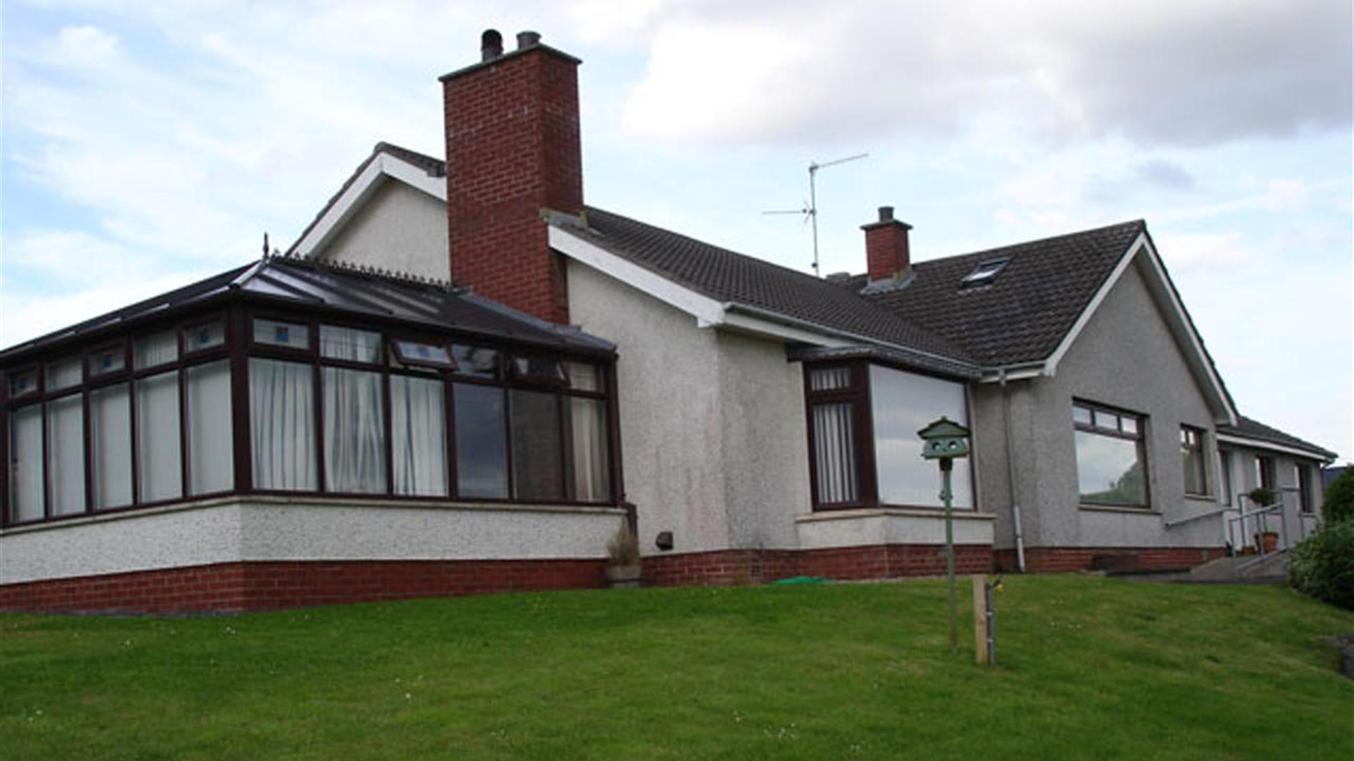Image shows outside view of the property with sun room