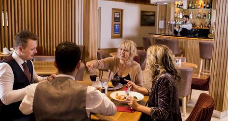 Image shows diners sitting at a table eating