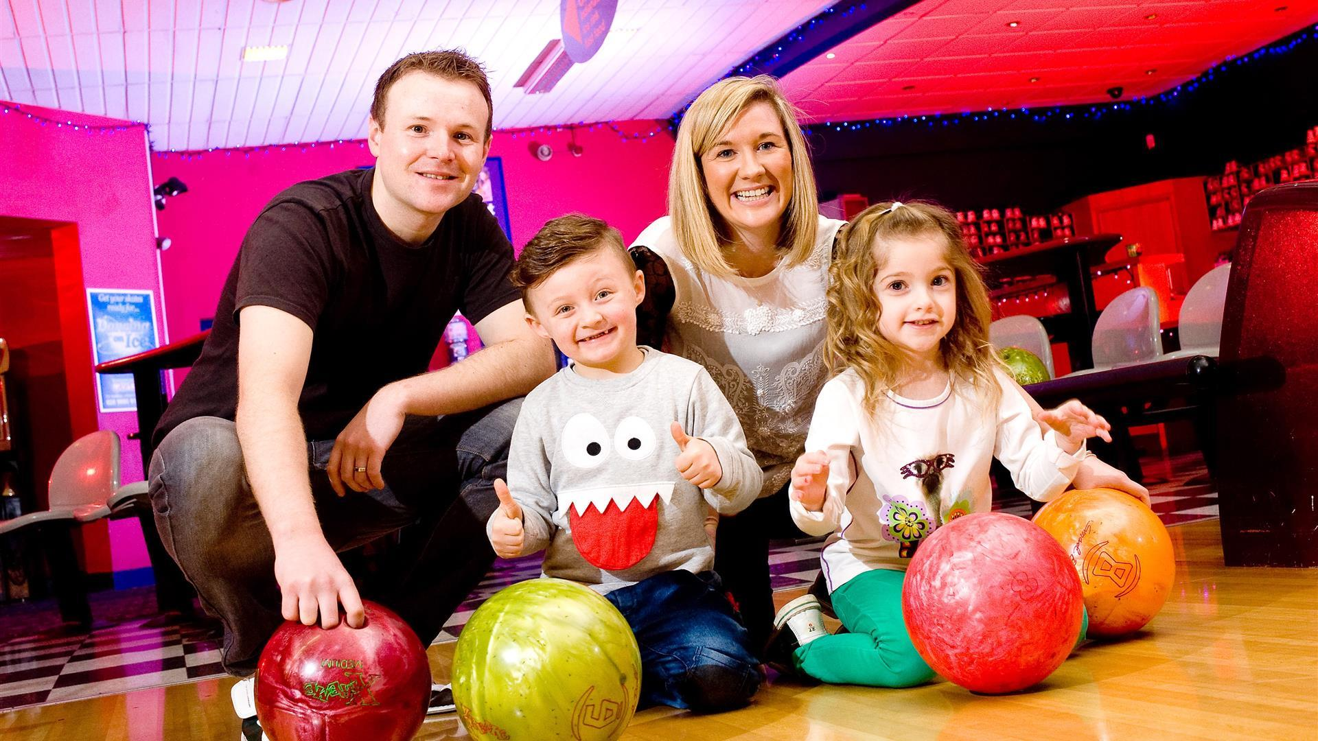 Image is of a family posing for a photo in the bowling alley