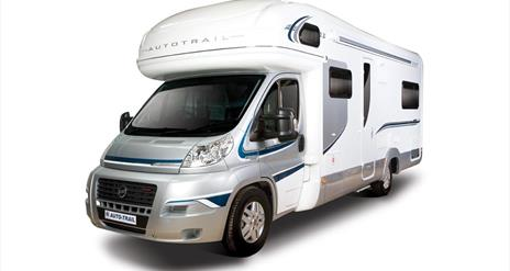 Image is of a silver and white motorhome