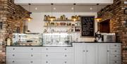 Image shows coffee shop area with menu board