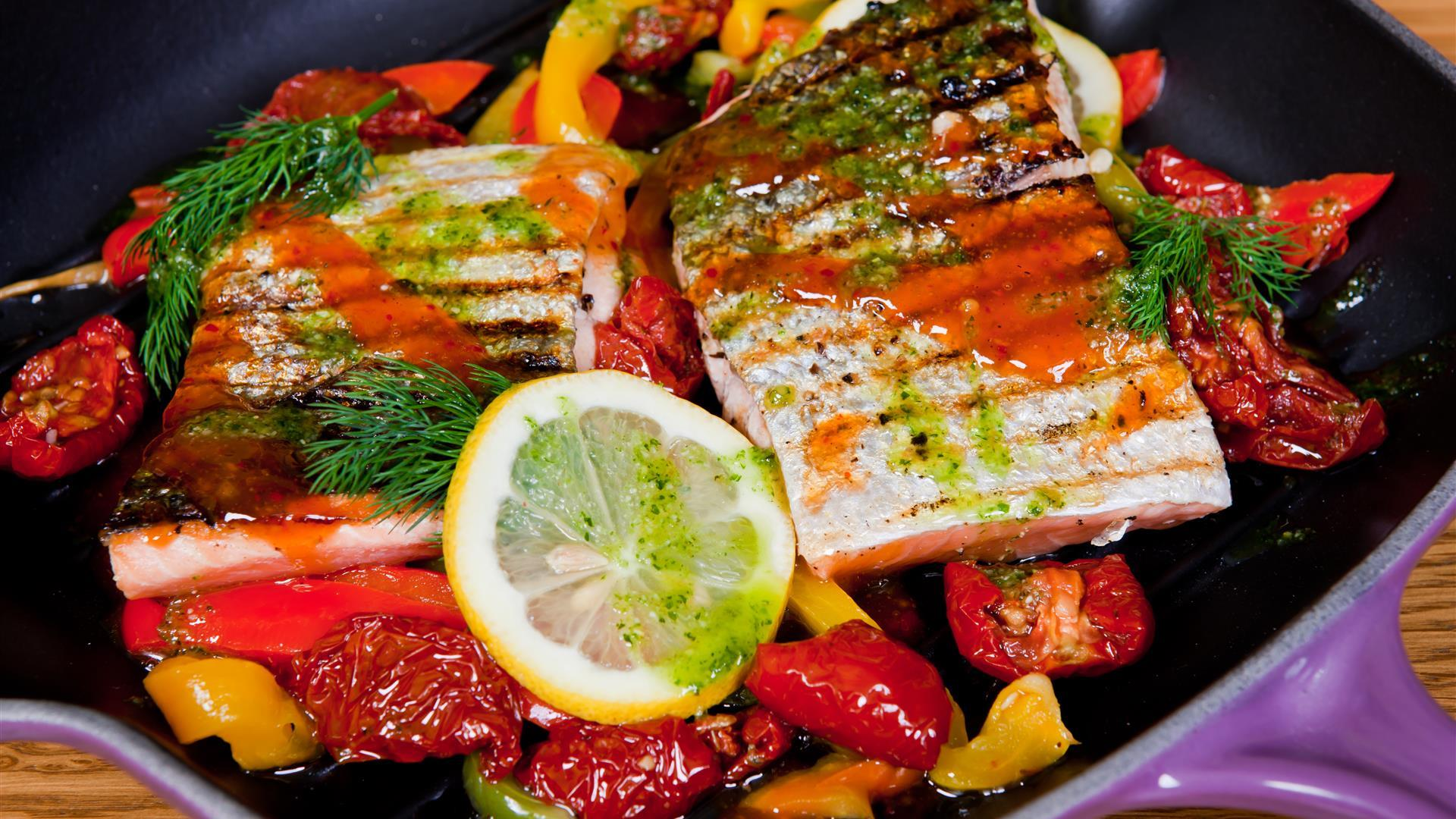 Image is of a fish, vegetables and lemon slice dish