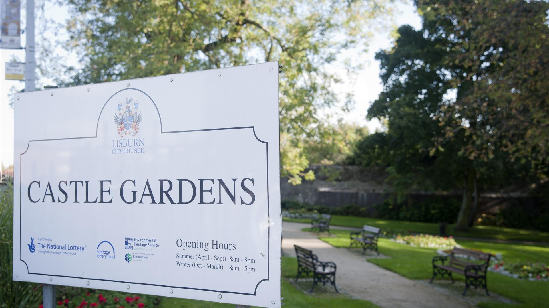 Image shows signage in the gardens with path and benches