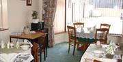 Image shows dining room of property with large window looking out onto courtyard