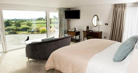 Shows image of double bedroom with large window looking out at countryside view