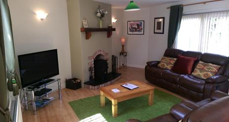 Image shows lounge area with leather sofas, fireplace, coffee table and TV