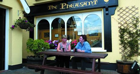 Images shows 2 females sitting and enjoying a drink at a picnic table outside the restaurant