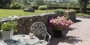 Image shows outside area with wrought iron table and chair, grassy area and view of the countryside beyond