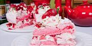 Image is of pink pavlova and strawberries